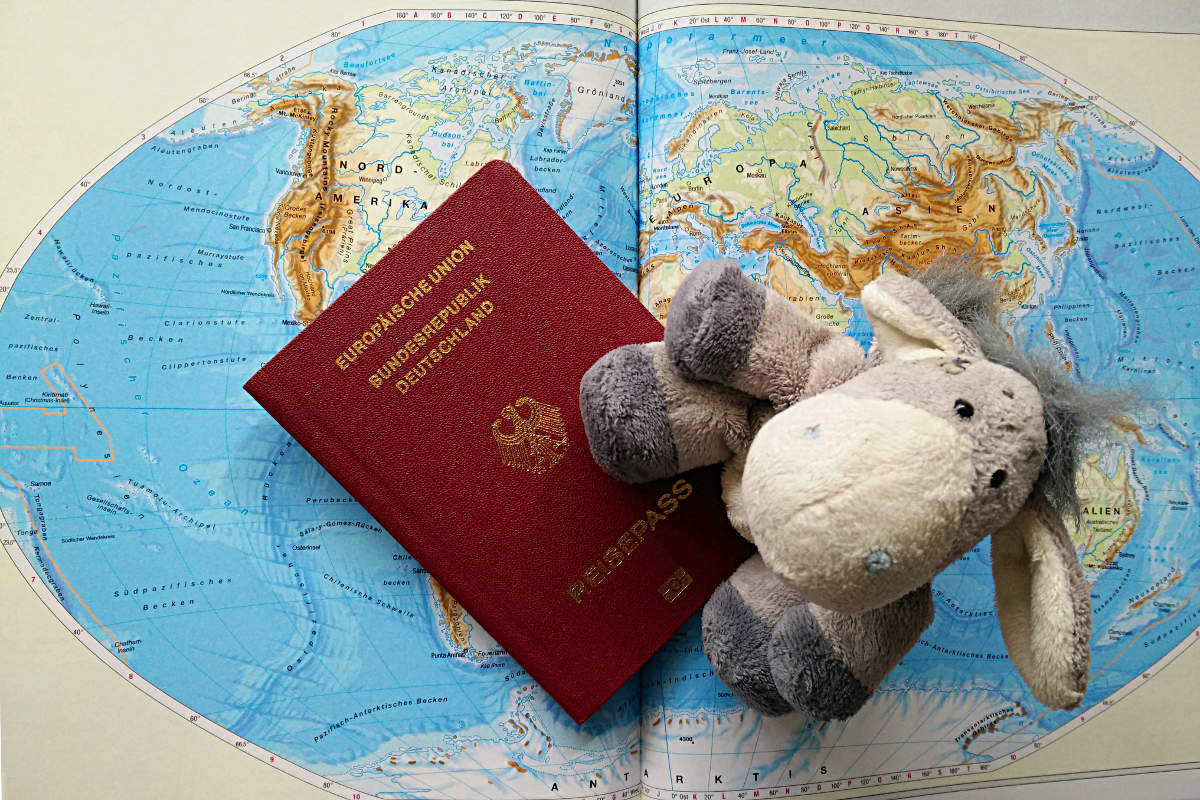 Der Esel unterwegs mit Reisepass und Weltkarte