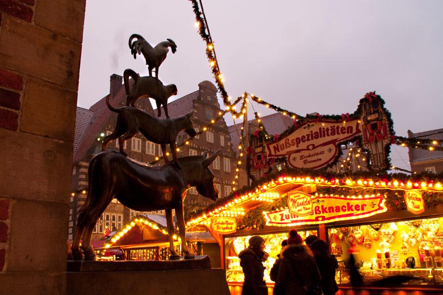 Die Bremer Stadtmusikanten blicken auf den Weihnachtsmarkt Bremen.