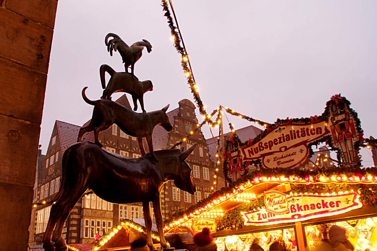 Die Bremer Stadtmusikanten mit Blick auf den Weihnachtsmarkt